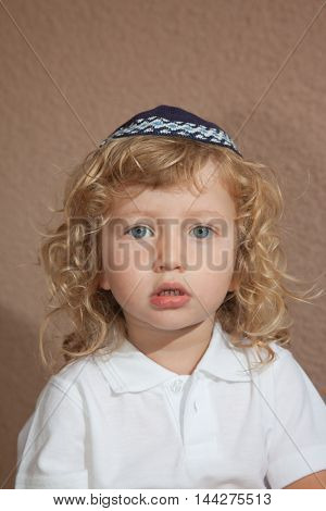 The charming little boy with long blond curls and blue eyes in the Jewish knitted skullcap. Autumn holiday of Sukkot