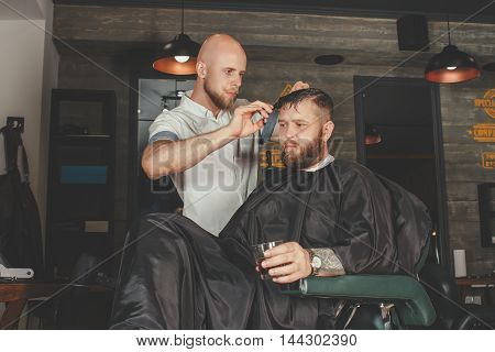 Serious Bearded Man Getting Haircut By Barber And Holding A Glass Of Whiskey While Sitting In Chair At Barbershop. Barbershop Theme poster