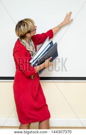 female office worker in a red dress with a pile of folders under her arm the other arm enthusiastically shows something on a white screen turned sideways to the audience