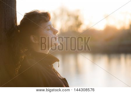 Side profile of peaceful nirvana young woman in coat with closed eyes by lake with soft brown autumn light