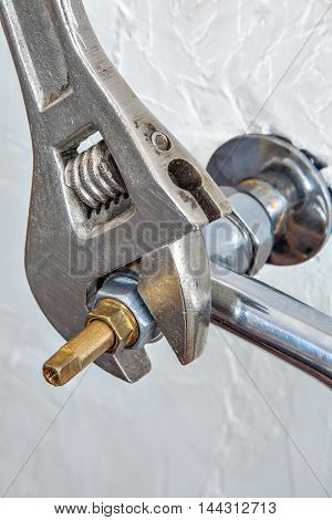 Close-up adjustable spanner plumbers screwing water faucet valve for tap.