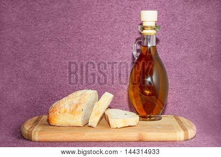 Close view of olive oil and sliced bread standing on cutting board