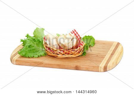Close view of champignons lying in small basket on cutting board isolated over white background