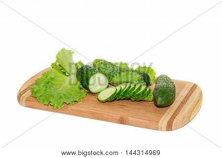 Cucumbers and green salad lying on cutting board isolated over white background