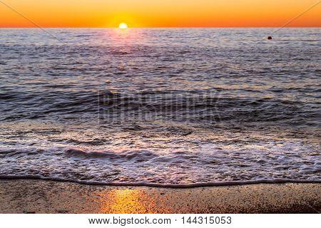 Foam Sea Wave Rushes Onto Seashore At Sunset