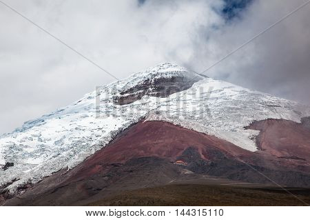 Cotopaxi volcano appears in the clouds light snow and pure ice