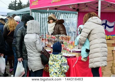 Children With Their Parents To Buy Sweets In A Street Tent On Th