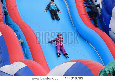 Baby Girl Is Riding And Screaming Fun On An Inflatable Slide On