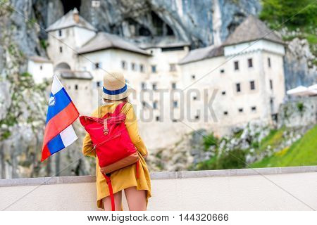 Young female traveler with slovenian flag standing near Predjama castle. This castle is a famous tourist attraction and a travel destination in Slovenia
