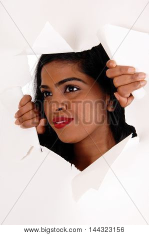 A pretty Indian woman with black hair looking trough a hole is a paper with red lips isolated for white background.
