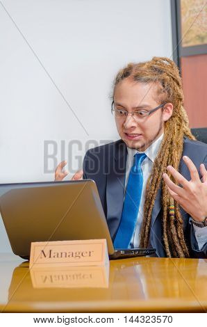 Handsome man with dreads and business suit sitting by desk having video conversation on laptop, young manager concept.