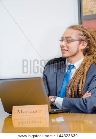 Handsome man with dreads and business suit sitting by desk, arms crossed, young manager concept.