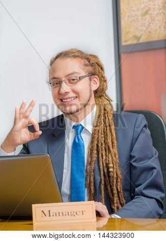 Handsome man with dreads and business suit sitting by desk looking at camera creating circle using fingers, positive body language, young manager concept.