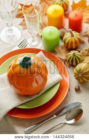 Thanksgiving dinner. Seasonal table setting with autumn leaves candles and pumpkins.