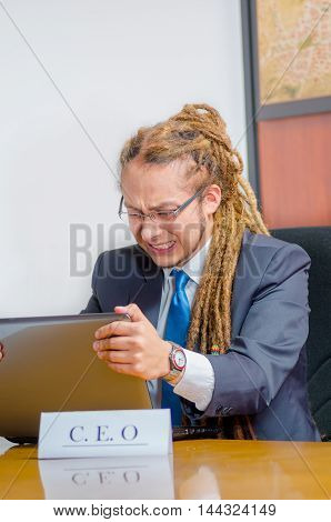 Handsome man with dreads and business suit sitting by desk holding onto laptop screen, frustrated facial expression, young manager concept.