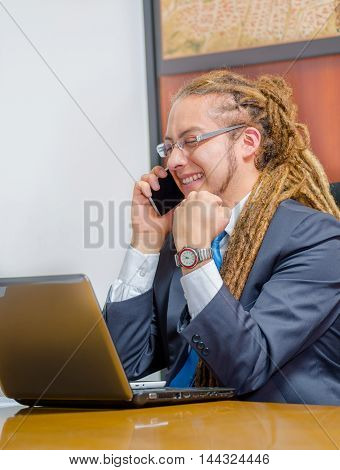 Handsome man with dreads and business suit sitting by desk talking on mobile phone, young manager concept.