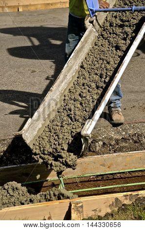 Wet mud ready mix concrete slides down a chute in a street curb repair job