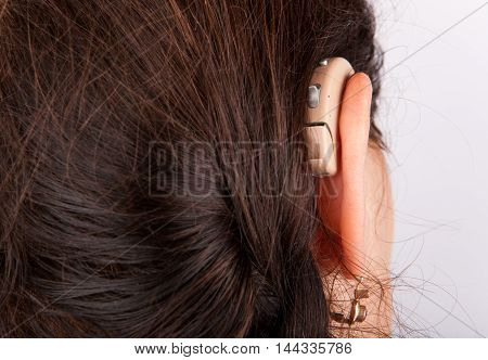 Close up of an woman's ear with hearing aid from back