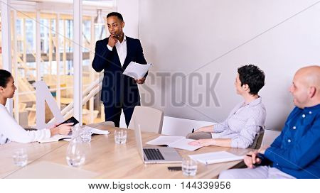 Businessman standing in front of 3 colleagues in board room busy giving a presentation about their company possibly entering into a collaboration with someone else.