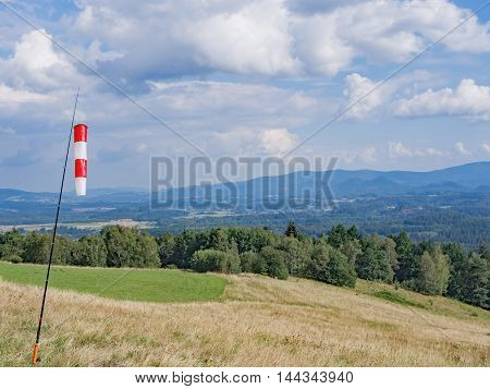 Red And White Wind Cone In A Hilly Landscape With Forest