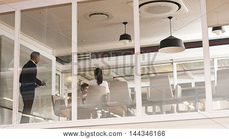 Mixed race businessman busy giving a presentation in a modern office with glass walls and several reflections on the glass walls