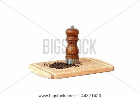 Close view of balck peper and peper mill standing on cutting board isolated over white background