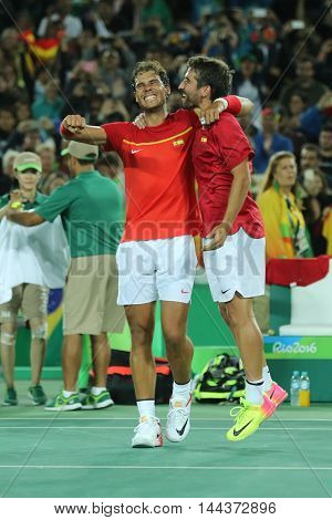 RIO DE JANEIRO, BRAZIL - AUGUST 12, 2016: Olympic champions Rafael Nadal (L) and Mark Lopez of Spain celebrate victory at men's doubles final of the Rio 2016 Olympic Games at the Olympic Tennis Centre