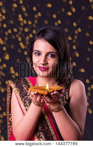happy diwali greeting card showing indian beautiful Girl holding a diya on diwali festival, asian girl and diya, over black background