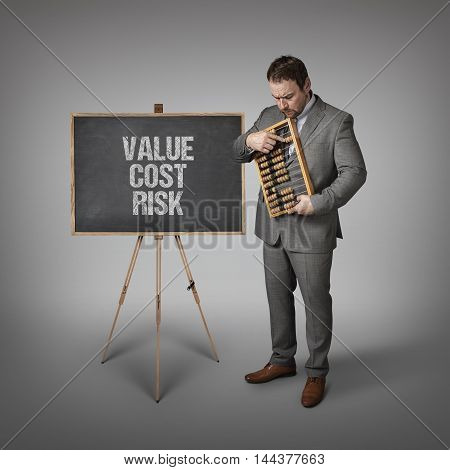 Value Cost Risk Risk text on blackboard with businessman and abacus