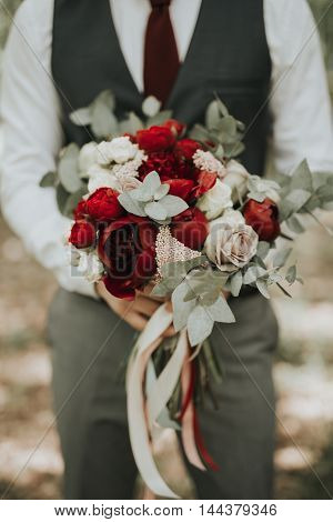 Portrait Of A Wedding Groom Posing  With Bouquet Of Flowers In H