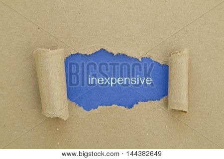 Inexpensive word written under torn paper .