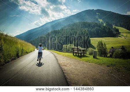 Young girl riding her bycicle along the street that from San Candido leads to Leinz Italy and Austria linked together