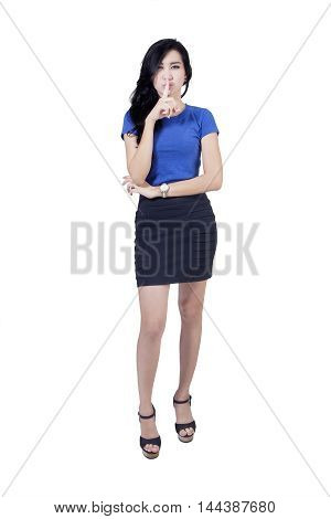 Full length of beautiful woman standing in the studio while making a silence gesture isolated on white background