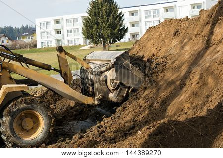Loader shovels in a pile of dirt at a construction site earth
