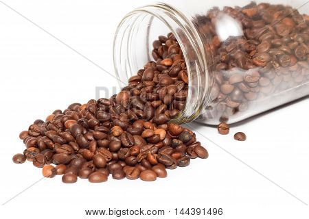 Scattered coffee beans near glass jar isolated over white background