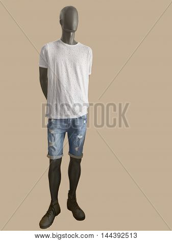 Male mannequin dressed in white t-shirt and shorts. Isolated on brown background. No brand names or copyright objects.