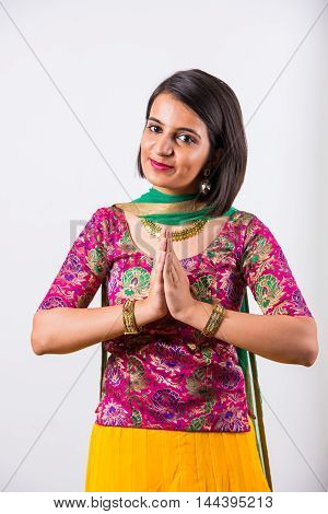 Happy indian yount girl or female in ethnic lehenga in namaskar pose or welcoming, isolated over white background. Traditional Indian Woman greeting with a smile.