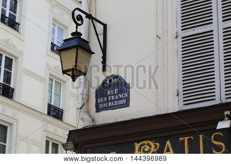 PARIS, FRANCE - MAY 13, 2016: There are fragments of typical old Parisian street: vintage lantern windows with banisters shutters.