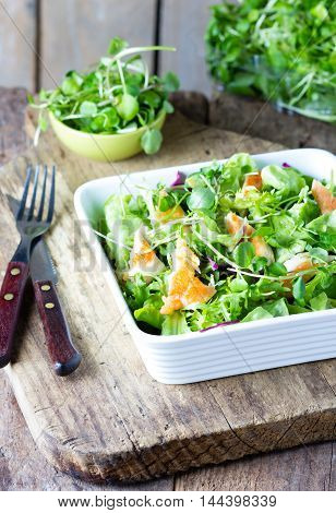 Fresh healthy vegetables lettuce arugula and chicken salad in white bowl on wooden rustic cutting table on wooden old background. Caesar cesar salad.