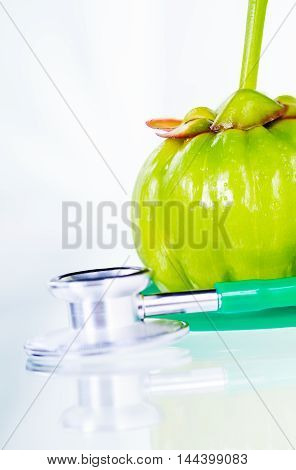 Garcinia cambogia fresh fruit and stethoscope on white. Garcinia atroviridis is spice plants and hydroxy citric acids (HCA) for good health. Shallow depth of field garcinia fruit in focus.