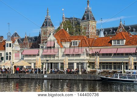 Amsterdam the Netherlands -October 03 2015: Tourists sitting at outdoor restaurant in Amsterdam. View of Amsterdam Central Station from water canal