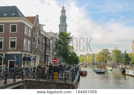 Amsterdam the Netherlands -October 03 2015: Tourists walking in historic city centre. View to Westerkerk (Western church)