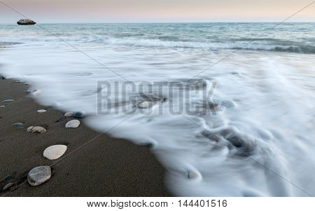 Pebbles on the beach on black sand and flowing sea water creating nice textures. Long exposure image.