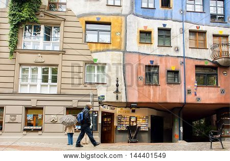 VIENNA, AUSTRIA - JUN 12, 2016: Tourist walking around house built with concept of Austrian artist Hundertwasser on June 12, 2016. Hundertwasserhaus built at 1985 and became the cultural heritage
