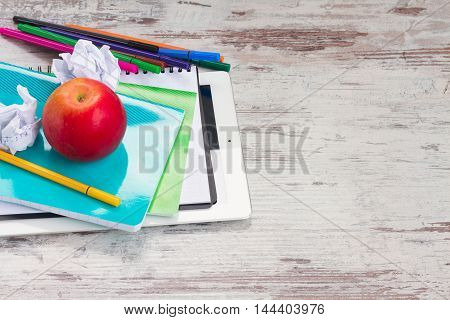 back to school frame with school supplies and tablet with empty screen on wooden desktop