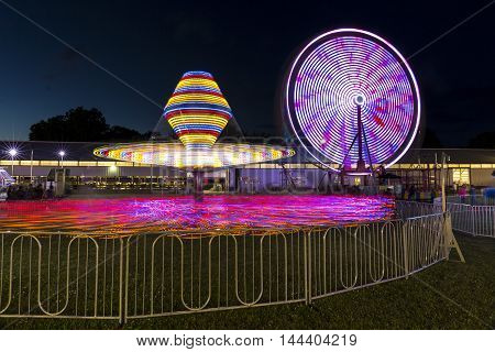Two carnival rides in motion at night.
