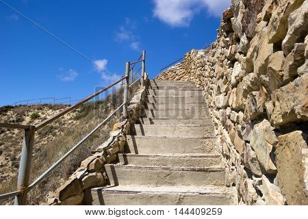 Concrete stairs ascending to top of hill. Bright blue sky over the hill. Rock wall handrail and dry grass. Close up. Selective focus on stairs.