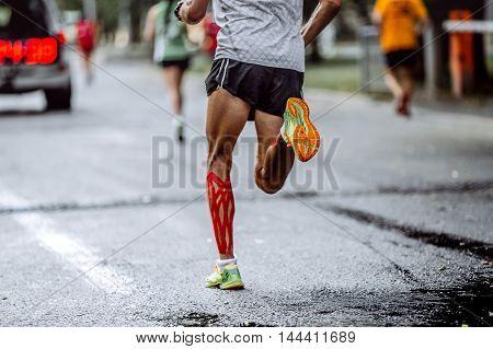 feet male athlete taping on calf muscles running city marathon
