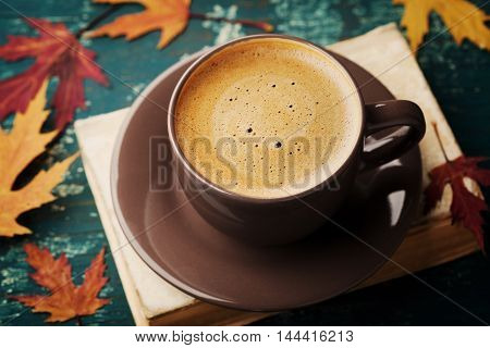 Coffee mug with old book and dry leaves on teal rustic table. Cozy breakfast. Vintage style