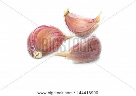 Cloves of unpeeled garlic isolated over white background